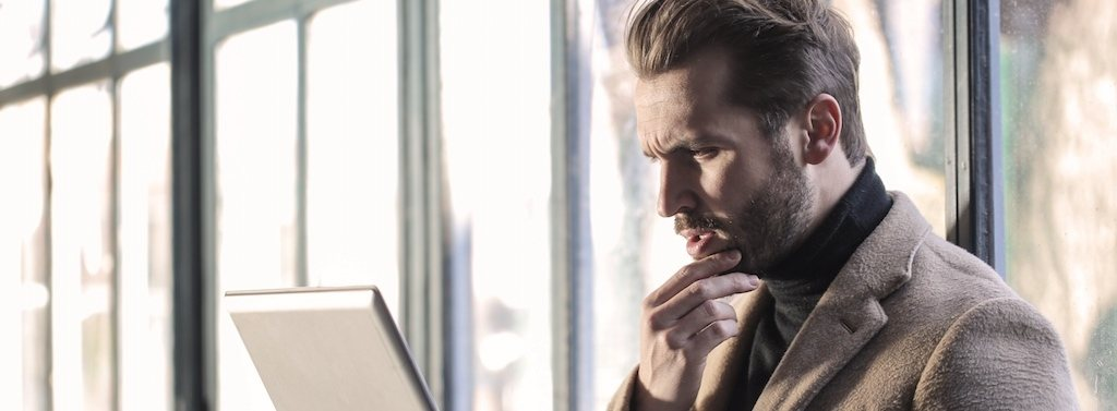 Frustrated man sitting on ground with laptop