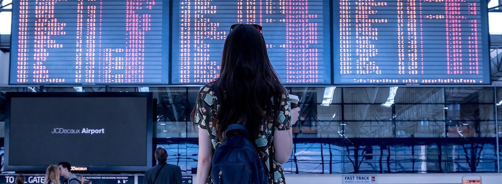 Woman looking at an airport departure board