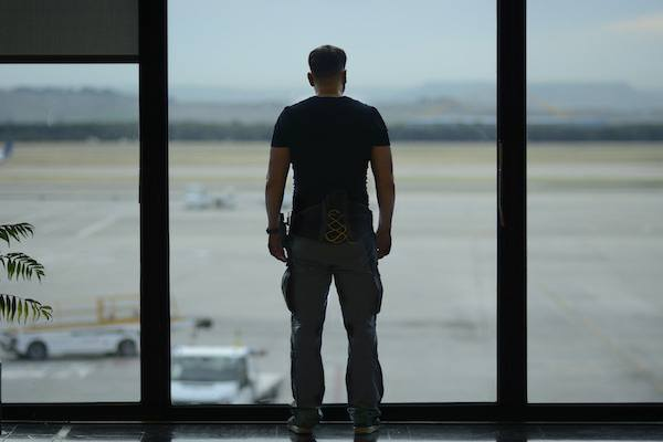 Man in an airport looking out of a window