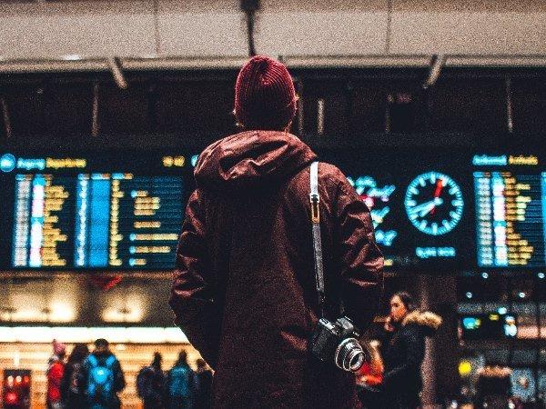 Un joven espera en un aeropuerto durante una escala.