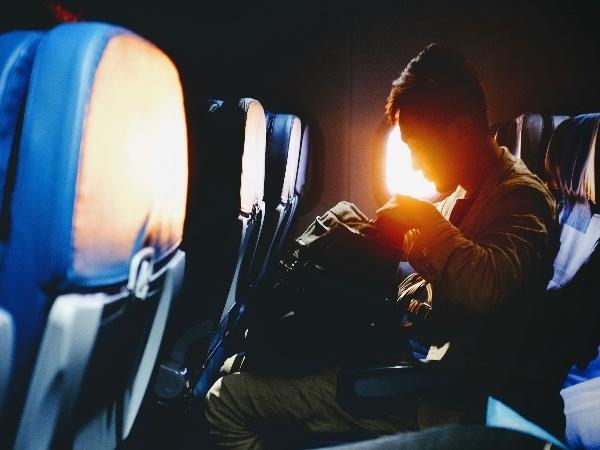 Un hombre con su equipaje de mano antes de comenzar un vuelo de larga distancia.