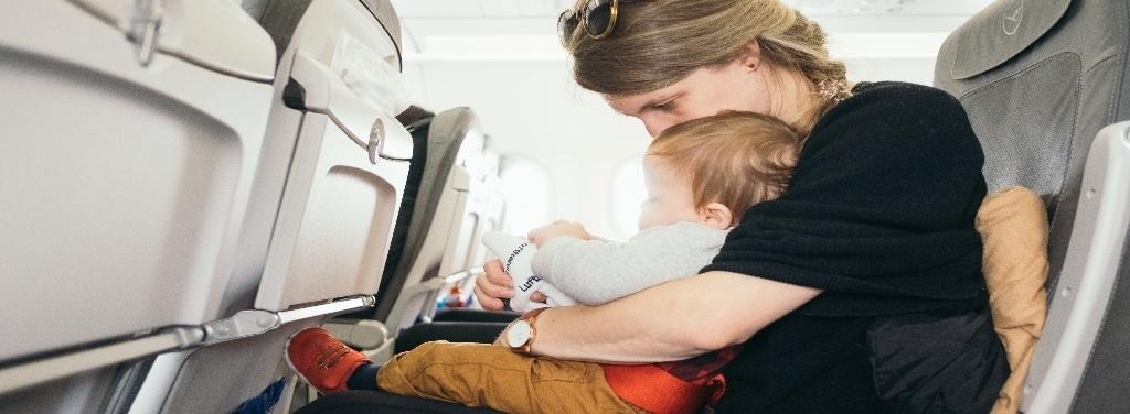 Una madre viaja con su hijo dentro de un avión.