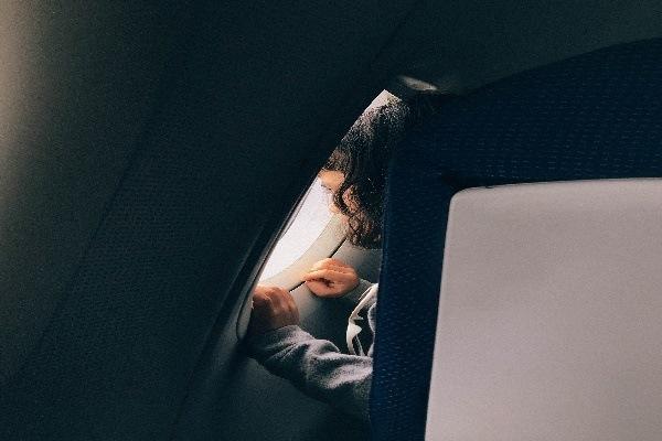 Una niña mira por la ventanilla en un avión.