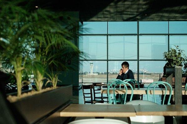 Uomo seduto nella caffetteria di un aeroporto