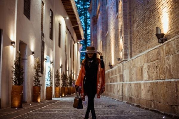 En kvinna klädd i sjal och klänning på stan