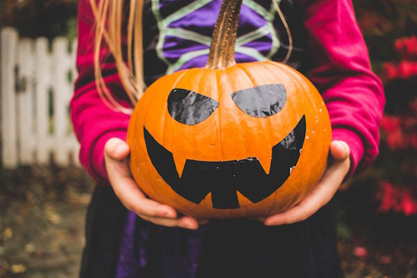 child holds a pumpkin