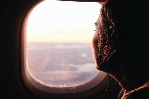 Una mujer mira por la ventanilla en un vuelo de larga distancia