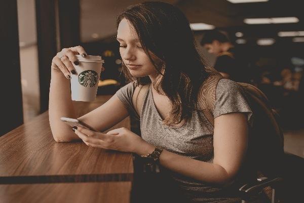 Una joven se toma un café en el aeropuerto mientras espera que salga su avión.