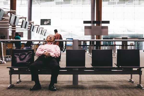Mann sover på flyplass