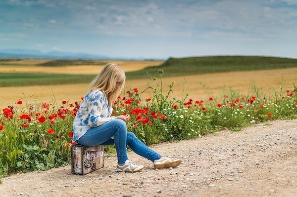 Woman waiting by field with suitcase