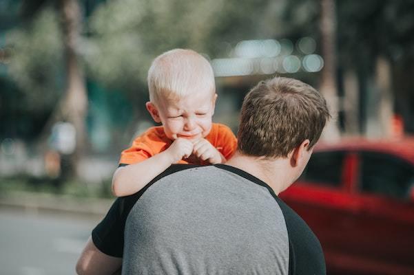 mann som holder en baby