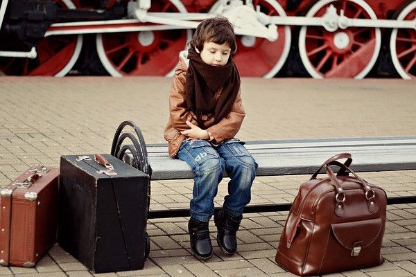 kid sitting on bench with suitcases waiting for self transfer flight