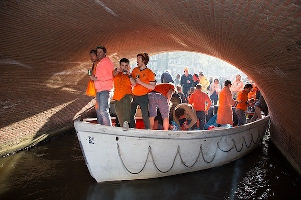 men wearing orange on a boat at King's Day in Amsterdam