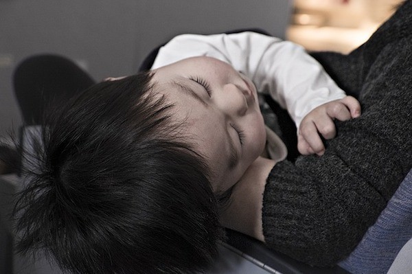 how to sleep on a plane for toddler sleeping in parent's arms