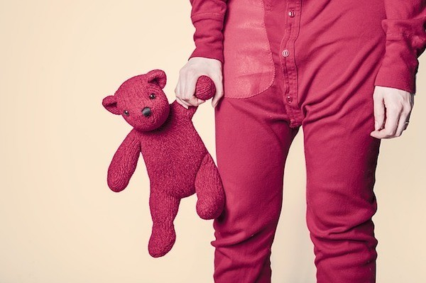 person in red pajamas holding a red teddy bear