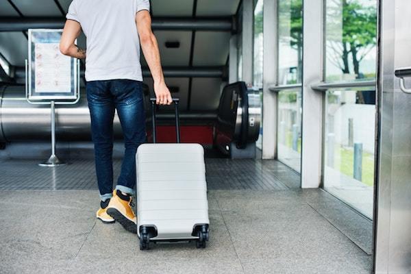 Hombre llevando una maleta con ruedes en el aeropuerto