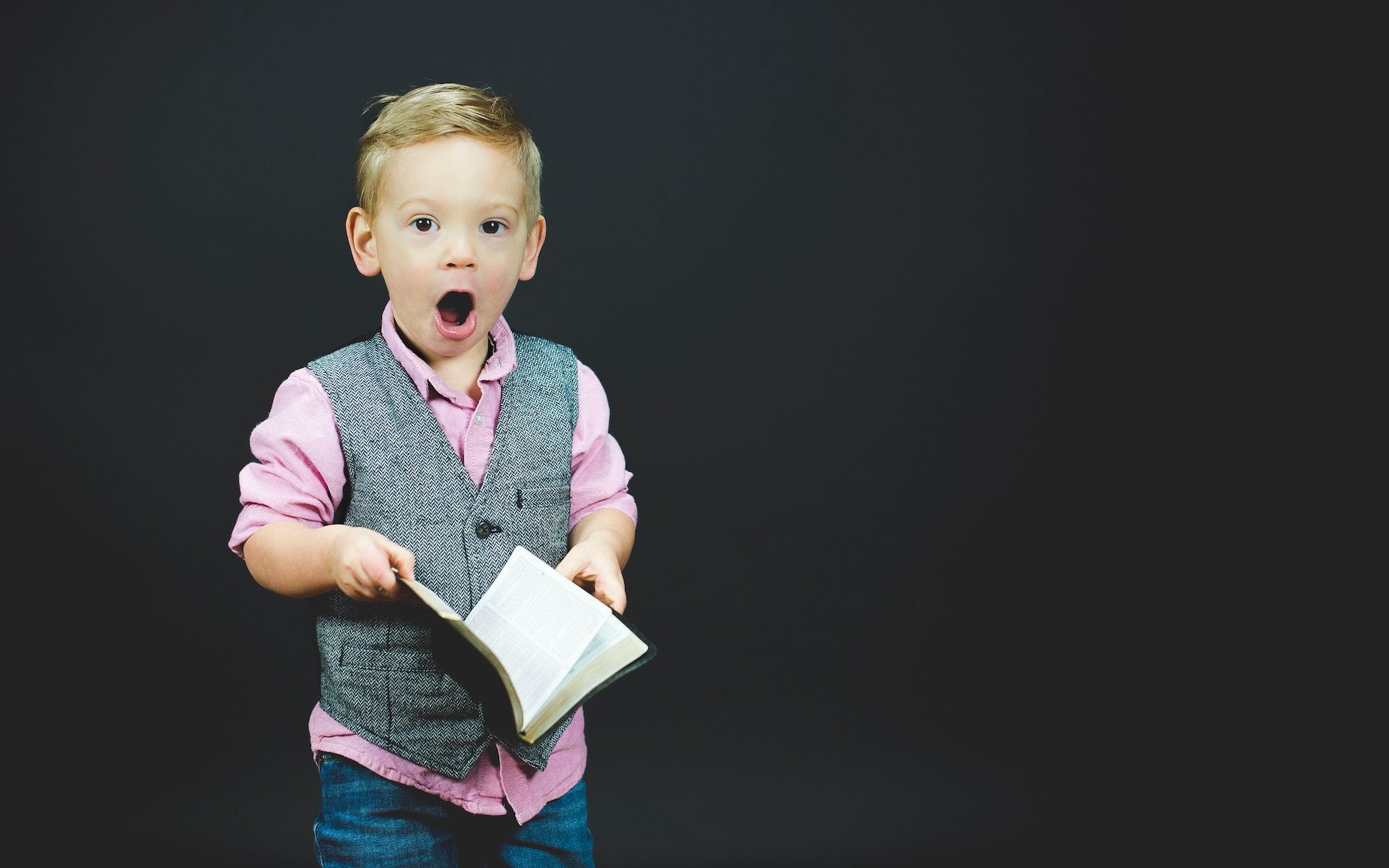 surprised boy holding a book