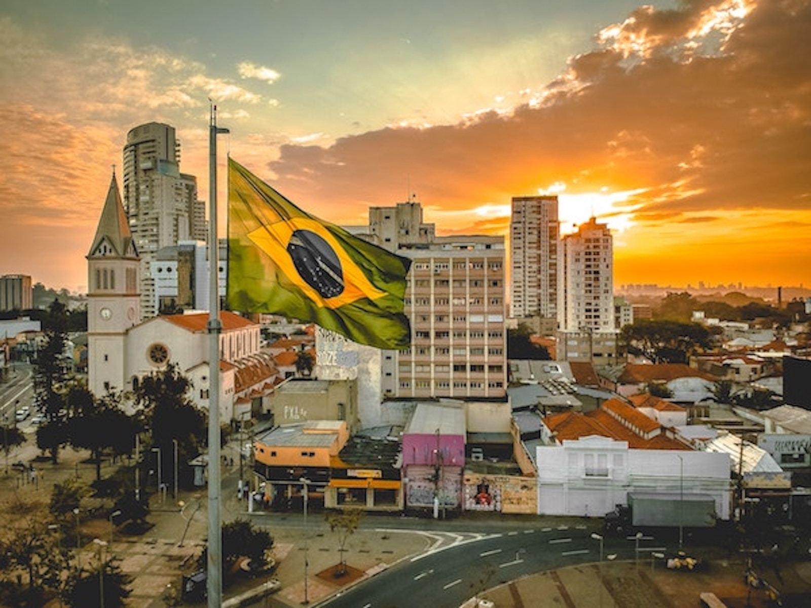 Brazil flag in front of sunset
